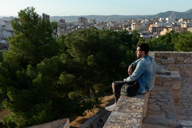 Jeune homme avec bonnet et veste cherche la ville. concept de style de vie, modèle.