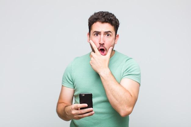 Jeune homme avec la bouche et les yeux grands ouverts et la main sur le menton, se sentant désagréablement choqué, disant quoi ou wow