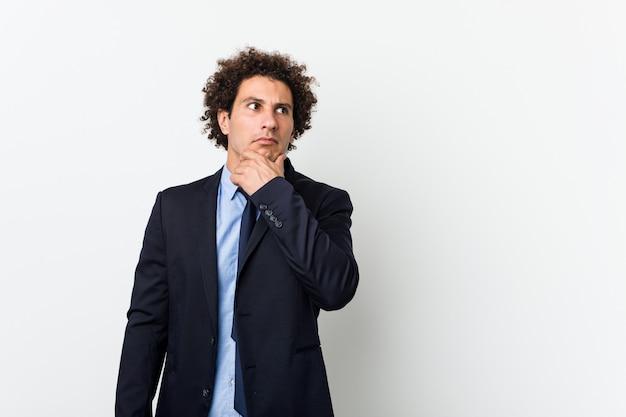 Jeune homme bouclé d'affaires sur fond blanc à la recherche de côté avec une expression douteuse et sceptique.