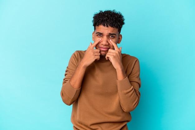 Jeune homme bouclé afro-américain sur bleu pleurer, mécontent de quelque chose, l'agonie et le concept de confusion.