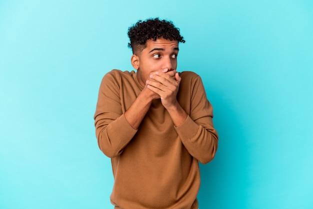 Jeune homme bouclé afro-américain isolé sur bleu réfléchi à la recherche d'un espace de copie couvrant la bouche avec la main.