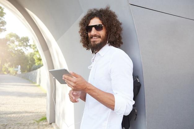 Jeune homme bouclé attrayant avec barbe souriant doucement, écoutant de la musique avec des écouteurs sur sa tablette