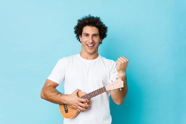 Jeune homme bouclé caucasien jouant ukelele acclamant sans soucis et excité. concept de victoire.