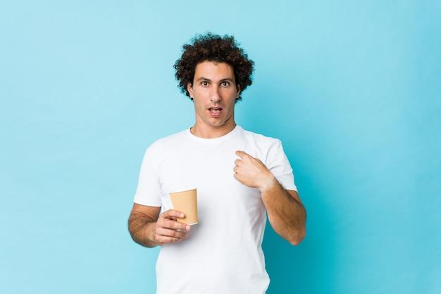 Jeune homme bouclé caucasien tenant un café à emporter surpris en se montrant, souriant largement.