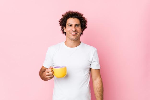 Jeune homme bouclé caucasien tenant une tasse de thé heureux, souriant et joyeux.