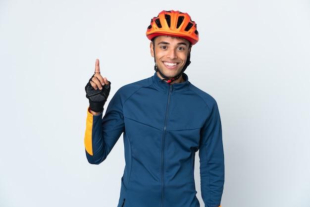 Jeune homme brésilien cycliste isolé sur mur blanc montrant et levant un doigt en signe de la meilleure