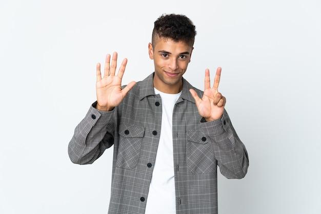 Jeune homme brésilien isolé sur blanc comptant huit avec les doigts