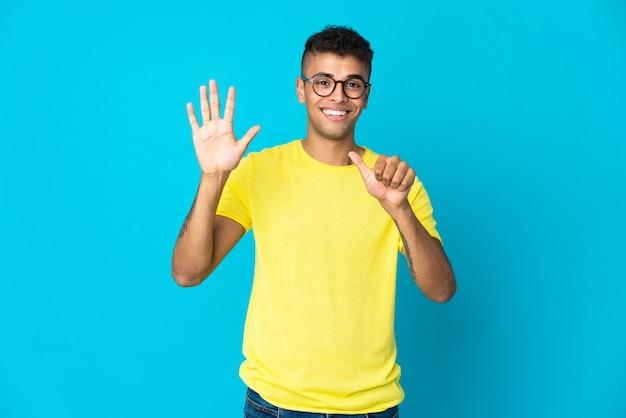 Jeune homme brésilien isolé sur fond bleu comptant six avec les doigts