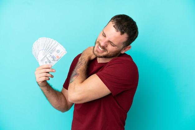 Jeune homme brésilien prenant beaucoup d'argent sur fond isolé souffrant de douleurs à l'épaule pour avoir fait un effort