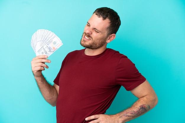 Jeune homme brésilien prenant beaucoup d'argent sur fond isolé souffrant de maux de dos pour avoir fait un effort