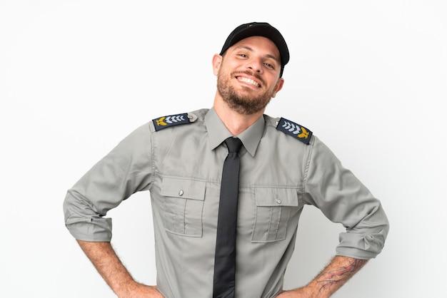 Jeune homme brésilien de sécurité isolé sur fond blanc posant avec les bras à la hanche et souriant