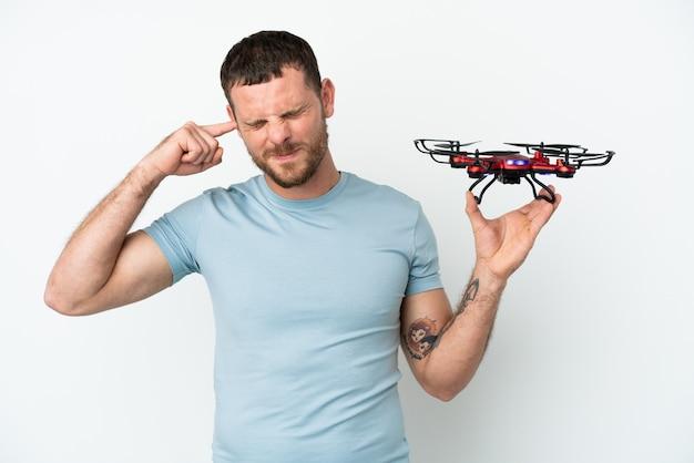Jeune homme brésilien tenant un drone isolé sur fond blanc frustré et couvrant les oreilles