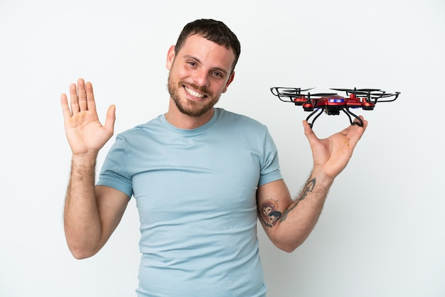 Jeune homme brésilien tenant un drone isolé sur fond blanc saluant avec la main avec une expression heureuse
