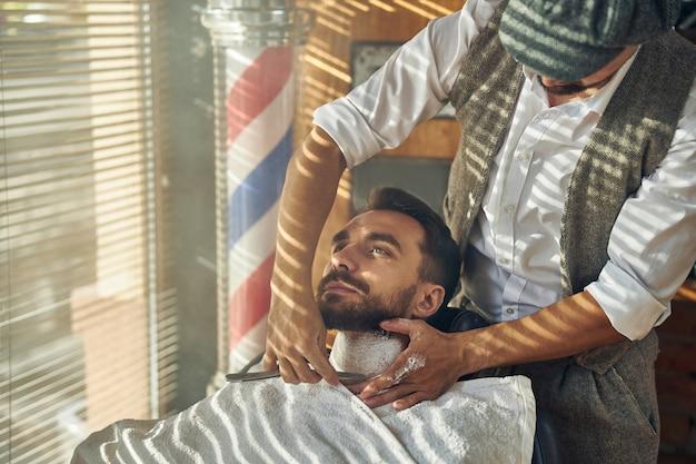 Jeune homme brune à l'air détendu dans un fauteuil tout en se rasant professionnellement chez un coiffeur