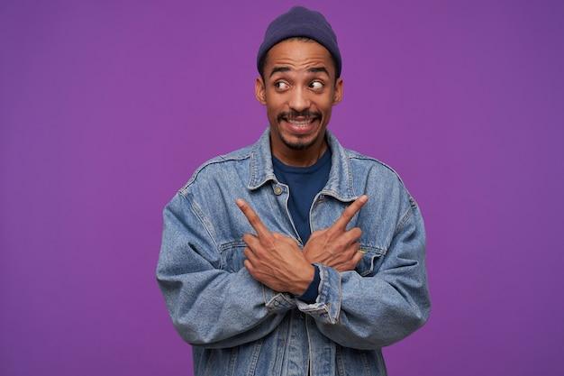 Jeune homme brune barbu à la peau sombre fronçant le front et montrant les dents tout en regardant confusément de côté, debout sur un mur violet avec les bras croisés