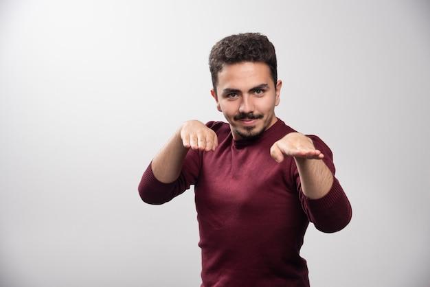 Un jeune homme brune debout et posant.