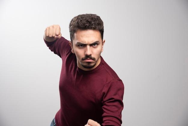 Un jeune homme brune debout et prêt à frapper.