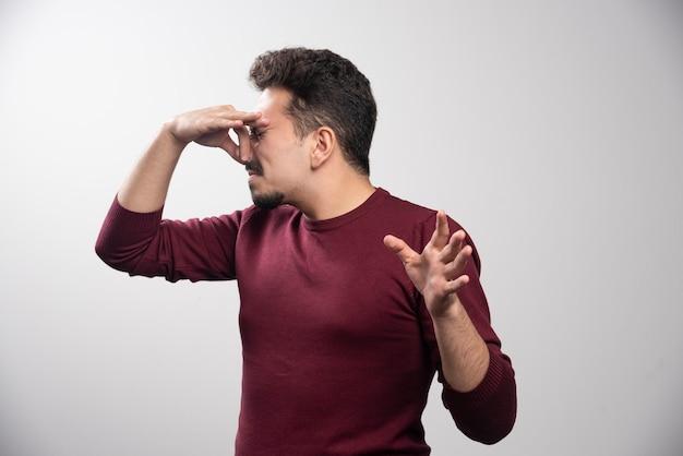 Un jeune homme brune dégoûté ferme son nez.