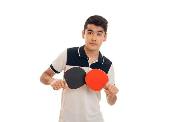 Jeune homme brune jouant au ping-pong isolé sur un mur blanc en studio