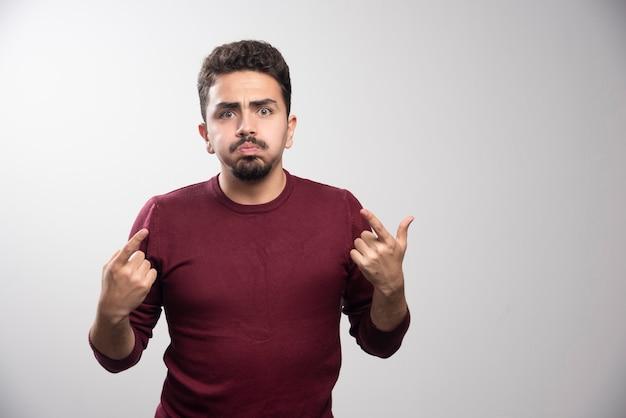 Un jeune homme brune montrant les doigts