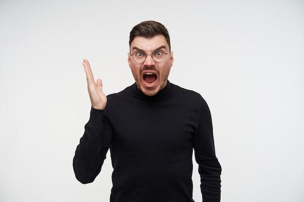 Jeune homme brune non rasée mécontent avec coupe de cheveux courte crier en colère