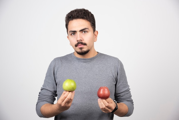 Jeune homme brune tenant deux pommes sur fond gris.