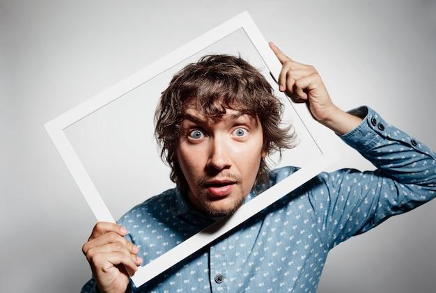 Jeune homme brunet portant chemise bleue et cadre de maintien
