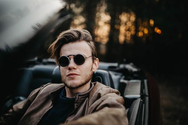 Jeune homme brutal à lunettes de soleil est assis dans une voiture décapotable de luxe