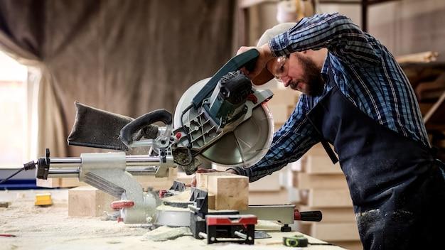 Jeune homme builder charpentier planche à scier avec scie circulaire en atelier