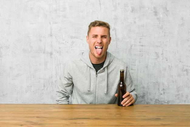 Jeune homme buvant une bière sur une table drôle et sympathique qui sort la langue.