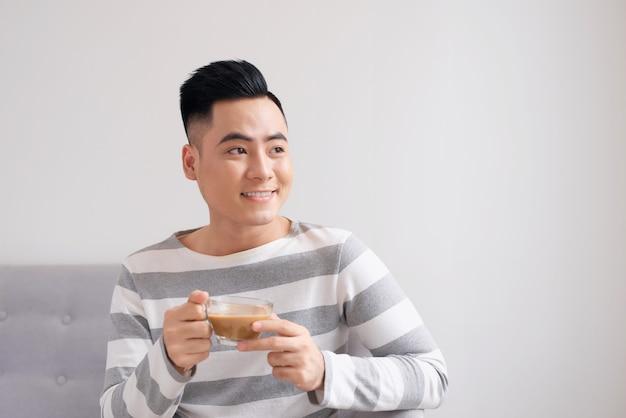 Jeune homme buvant du café dans un canapé.
