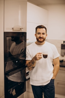 Jeune homme buvant du café à la maison