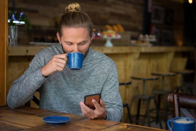 Jeune homme buvant du café tout en utilisant un téléphone intelligent au café