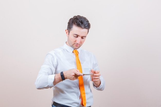Jeune homme buvant du café turc en chemise blanche, cravate et regardant attentivement