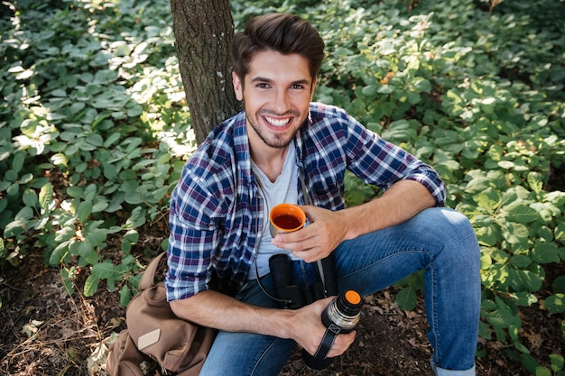 Jeune homme buvant du thé en forêt