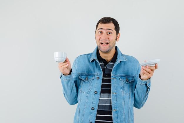 Jeune homme buvant du thé en t-shirt, veste et à la joyeuse