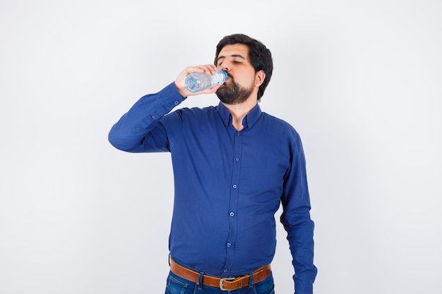 Jeune homme buvant de l'eau en chemise bleue et jeans et regardant sérieux, vue de face.