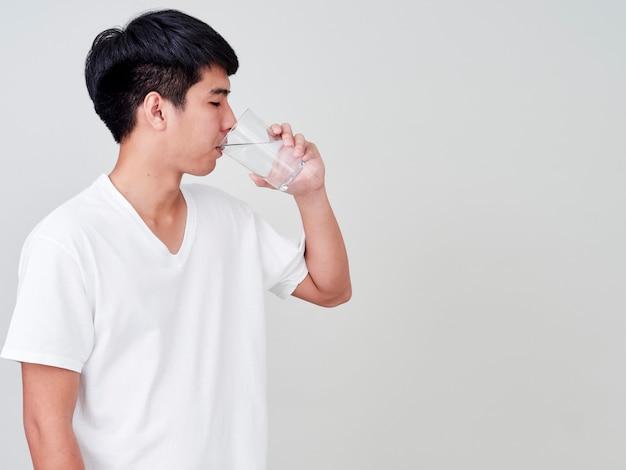 Jeune homme buvant de l'eau en verre.