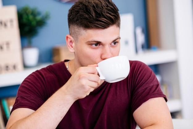 Jeune homme buvant à la tasse