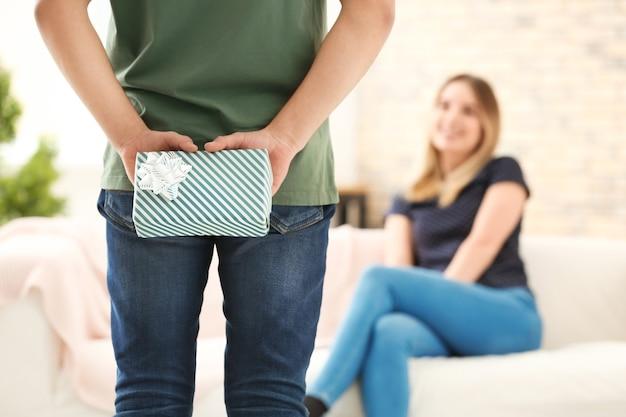 Jeune homme cachant un cadeau pour sa petite amie derrière son dos à la maison