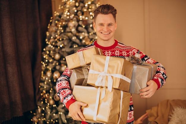 Jeune homme avec des cadeaux de noël