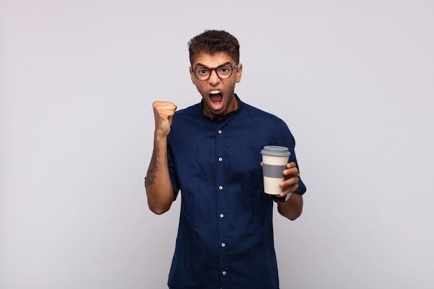 Jeune homme avec un café criant agressivement avec une expression de colère ou avec les poings fermés célébrant le succès