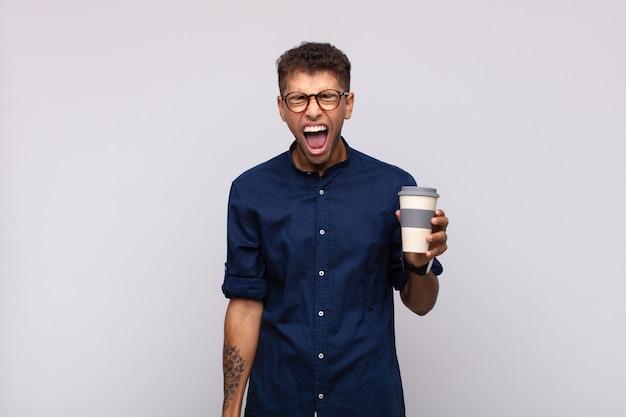 Jeune homme avec un café criant de manière agressive, à la très en colère, frustré, indigné ou ennuyé, criant non