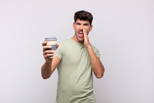 Jeune homme avec un café se sentant heureux, excité et positif, donnant un grand cri avec les mains à côté de la bouche, appelant