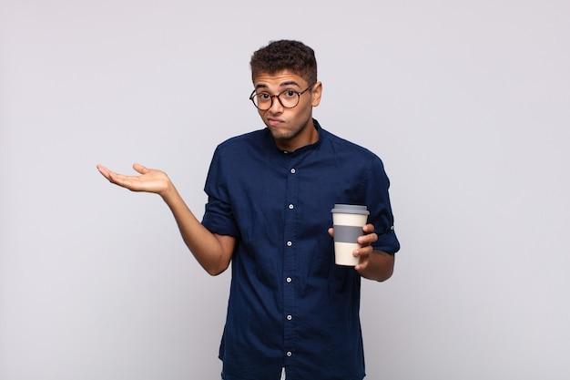 Jeune homme avec un café se sentant perplexe et confus, doutant, pondérant ou choisissant différentes options avec une expression amusante