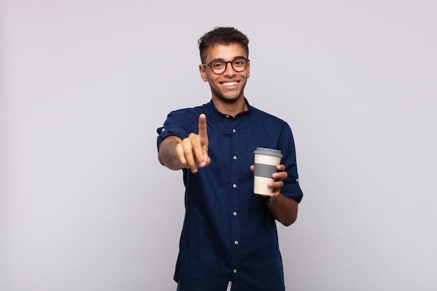 Jeune Homme Avec Un Café Souriant Fièrement Et En Toute Confiance Faisant Le Numéro Un Pose Triomphalement, Se Sentant Comme Un Leader Photo Premium