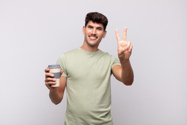 Jeune homme avec un café souriant et à la sympathique, montrant le numéro deux ou seconde avec la main vers l'avant, compte à rebours