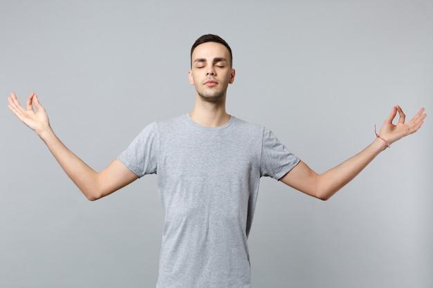 Jeune homme calme dans des vêtements décontractés en gardant les yeux fermés, se tenir la main dans un geste de yoga relaxant en méditant