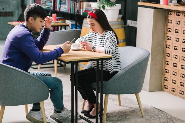 Jeune homme calme en tenue décontractée assis avec une jolie dame et souriant pendant que chacun d'eux regarde les écrans de smartphones