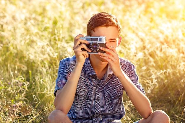 Un jeune homme avec une caméra prenant des photos du fond naturel rayons de soleil teinté